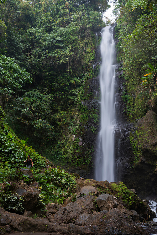 Bali, Indonesia - September 23, 2017: A tourist walks on trail at Melanting Waterfall, a popular hiking destination on the outskirts of Munduk, Bali.