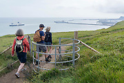 Overlooking cross-Channel ferries and Dover Docks harbour wall in the distance, walkers stride along the clifftop footpath, near the edge of Englands iconic White Cliffs, under threat from chalk and soil erosion, on 27th July, at Langdon Bay, Dover, in Kent, England.