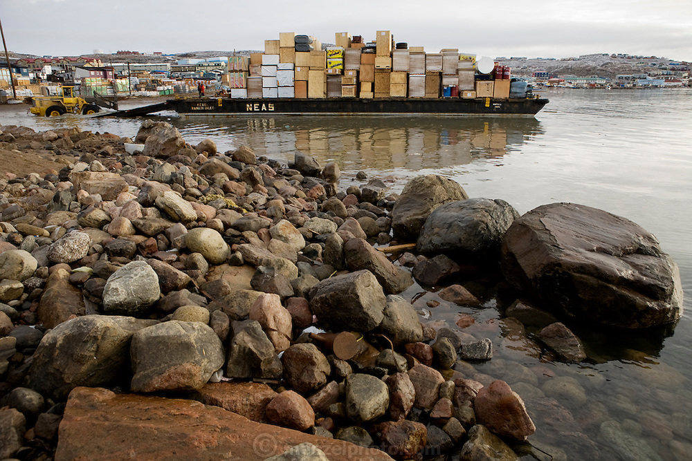 """A barge carrying food and supplies from the last cargo ship of the season is offloaded onto the rocky beach at low tide in Iqaluit, Nunavut, Canada. (From the book What I Eat, Around the World in 80 Diets.) Pack ice typically closes regional shipping lanes from October until early July. """"Iqaluit"""" means 'place of many fish'."""