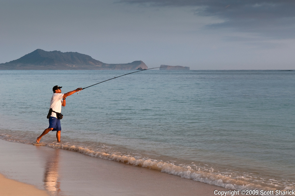 A man casting a fishing pole out into Kaneohe Bay in Hawaii.