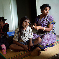 Kayalvizhi plaits Vijyashree's hair for school while Vijitha applies a bindi and powders her face. Kayalvizhi married the girls' father after the tsunami. <br />