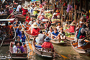 """10 JULY 2011 - DAMNOEN SADUAK, RATCHABURI, THAILAND:  Tourists in boats visit the """"floating market"""" in Damnoen Saduak, Thailand, about two hours south of Bangkok. The Thai countryside south of Bangkok is crisscrossed with canals, some large enough to accommodate small commercial boats and small barges, some barely large enough for a small canoe. People who live near the canals use them for everything from domestic water to transportation and fishing. Some, like the canals in Amphawa and nearby Damnoensaduak (also spelled Damnoen Saduak) in Rajburi  province (also spelled Ratchaburi) are also relatively famous for their """"floating markets"""" where vendors set up their canoes and boats as floating shops.     PHOTO BY JACK KURTZ"""