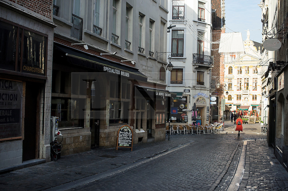 """© Licensed to London News Pictures. 23/11/2015. Brussels, Belgium. A woman walks down A deserted street at 2pm in central Brussels where the city is currently on """"lockdown"""" amid """"imminent threat"""" of Paris-style bomb and gun attacks. Photo credit: Ben Cawthra/LNP"""