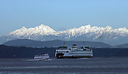 With a fresh coating of snow, almost the entire Olympic Mountain Range is on display behind The Washington State Ferry Tacoma and the West Seattle Sightseer, a passenger-only ferry heading to downtown Seattle.<br />