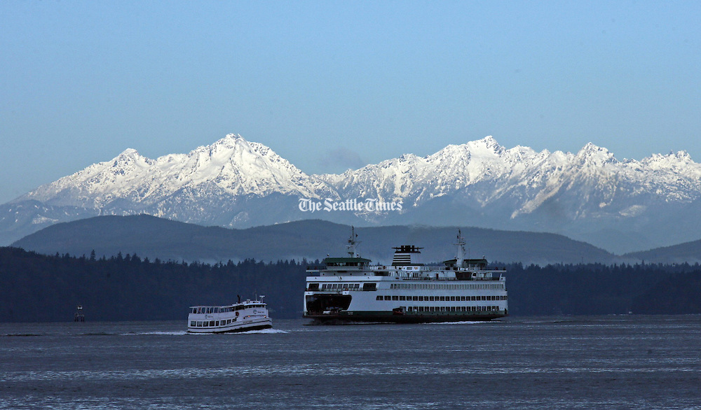 With a fresh coating of snow, almost the entire Olympic Mountain Range is on display behind The Washington State Ferry Tacoma and the West Seattle Sightseer, a passenger-only ferry heading to downtown Seattle.<br /> <br /> Greg Gilbert / The Seattle Times