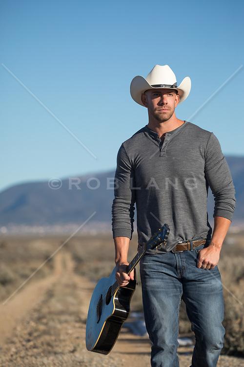 cowboy with a guitar walking down a dirt road