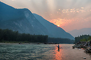 David Higman spey casting at sunrise with smokey skies. Dean River, BC.