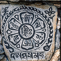 A mani stone with a Tibetan Buddhist parayer rest beside the trail to Mount Everest in the Khumbu Region of Nepal.