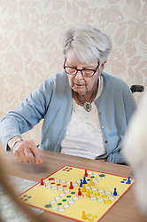 Senior woman playing ludo board game in rest home