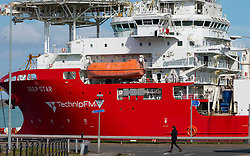 Leith, Edinburgh, Scotland, UK. 7 April 2020. In the third week of the nationwide coronavirus lockdown life in Leith continues although the streets are mostly deserted and shops closed. Pictured; Woman walks past offshore vessel Berthed in Leith docks. Iain Masterton/Alamy Live News.