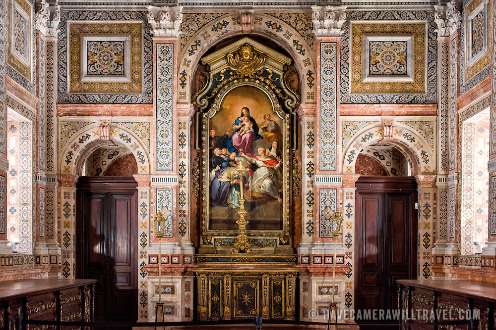 """LISBON, Portugal - The Sacristy was completed in 1716 and its walls are covered in polychrome marble inlays. The ceiling is decorated with an oil on canvas painting that features an """"Agnus Dei"""" (Lamb of God) in its center, surrounded by profuse floral decoration with allegories of the Canons Regular of St. Augustine and the City of Lisbon. The long wooden chests lining each side are made of Brazilian jacaranda and are designed to store the sacred vestments. Under the floor are 12th century anthropomorphic tombs that were discovered during restoration work. They are the tombs of the Teutonic crusaders who helped the first king, Afonso Henriques, in the conquest of Lisbon. The Monastery of São Vicente de Fora is a 17th-century church and monastery in the Alfama neighborhood of Lisbon. It features ornately decorated sections in the Baroque style as well as the Braganza Pantheon, where the kings who ruled Portugal between 1640 and 1910 are interred."""