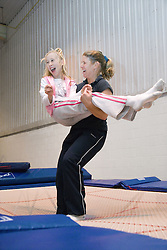 Visually impaired girl with teacher at trampolining youth group event run by NRSB,