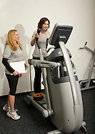 Monroe, New York - A instructor watches a woman use the exercise equipment at the new South Orange Family YMCA on Wednesday, Feb. 16, 2011.