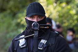 Aylesbury Vale, UK. 1st October, 2020. A member of the National Eviction Team uses a surveillance camera during the eviction of anti-HS2 activists from a wildlife protection camp in ancient woodland at Jones' Hill Wood. Around 40 environmental activists and local residents, some of whom living in makeshift tree houses 60 feet above the ground, were present during the evictions at Jones' Hill Wood which had served as one of several protest camps set up along the route of the £106bn HS2 high-speed rail link in order to resist the controversial infrastructure project.