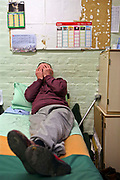 An elderly inmate relaxing on the bed in his cell in the Vulnerable Prisoners Unit. HMP Wandsworth, London, United Kingdom.