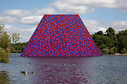 Art installation 'The Mastaba', by artist Christo, installed on the Serpentine lake in Hyde Park on June 18th 2018 in London, United Kingdom. The sculpture consists of 7,506 stacked barrels, painted in shades of red, white, blue and mauve. The completed piece forms part of an exhibition by Christo and his late wife, Jeanne-Claude's work, entitled Christo and Jeanne-Claude: Barrels and The Mastaba 19582018 to be held at The Serpentine Gallery.