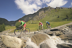 Three mountain bikers crossing stream on mountain, Zillertal, Tyrol, Austria