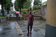 Omar dances in the rain whilst on the phone to a friend.