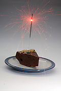 Birthday cake, a slice of chocolate cake with a burning firecracker