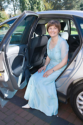 Woman; who is undergoing chemotherapy treatment for breast cancer; on her wedding day arriving by car at the registry office,