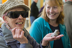 Visually impaired people with carers on outing to Denby Pottery. With clay frog.
