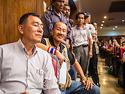 14 DECEMBER 2013 - BANGKOK, THAILAND: People line up against the wall to listen to speakers at the anti-government reform forum in Bangkok. The Thai anti-government movement, called the People's Democratic Reform Committee (PRDC) sponsored a forum Saturday to establish guidelines for political reform in Thailand. The opposition leader, Suther Thaugsuban, said his movement will not participate in a similar forum, sponsored by the government scheduled for Sunday. Thailand's political impasse continues with the opposition calling for the caretaker government of Prime Minister Yingluck Shinawatra to step down. Yingluck has, so far, refused to step down from her caretaker roll. Crowds at the anti-government rallies have shrunk substantially since the collapse of the government earlier in the week.        PHOTO BY JACK KURTZ