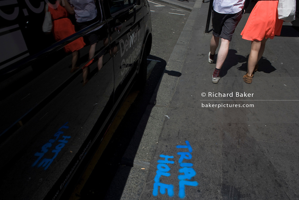"""Blue stencilled painted words saying """"trial Hole"""" seen on London street pavement."""