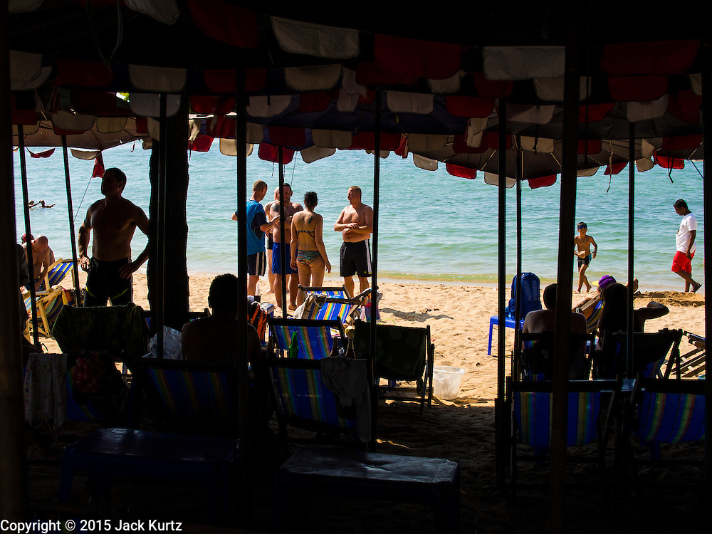 06 JANUARY 2015 - PATTAYA, CHONBURI, THAILAND:  Tourists framed through beach umbrella poles on Pattaya beach. The Thai government has announced plans to clean up Pattaya beach, one of the most famous beaches in Thailand. Pattaya is about 2.5 hours from Bangkok. They plan to reduce the number of umbrella and chaise lounge vendors on the beach and regulate the personal watercraft and parasailing vendors on the beach. The government has already cleaned up beaches on Phuket island and Hua Hin.   PHOTO BY JACK KURTZ