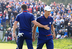 Team Europe's Rory McIlroy (left) and Thorbjorn Olesen react on the fourteenth during the Fourballs match on day one of the Ryder Cup at Le Golf National, Saint-Quentin-en-Yvelines, Paris.
