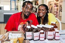 """Siblings Roniel Allembert (L) and Tiona Allembert are second generation beekeepers from St. Croix.  With over 350 hives, the pair present candles, lip balm, candles, soaps and more made with bee byproducts.  The VI Department of Agriculture hosts the second annual Fresh Beekeeping """"Buzzaar on St. Thomas.  The event which provided education and outreach featured an observation bee hive, and byproducts of hive production including soaps, balms, wines, candles, and beekeeping supplies.  Tutu Park Mall.  22 September 2012.  © Aisha-Zakiya Boyd"""