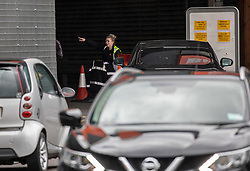 © Licensed to London News Pictures. 30/04/2020. London, UK. A B&Q worker directs traffic as cars enter the DIY store in New Malden. B&Q has opened all its stores in the UK today after closing for over a month due to the lockdown rules as the Prime Minister Boris Johnson will lead his first Downing Street briefing since falling ill with the coronavirus disease. Photo credit: Alex Lentati/LNP