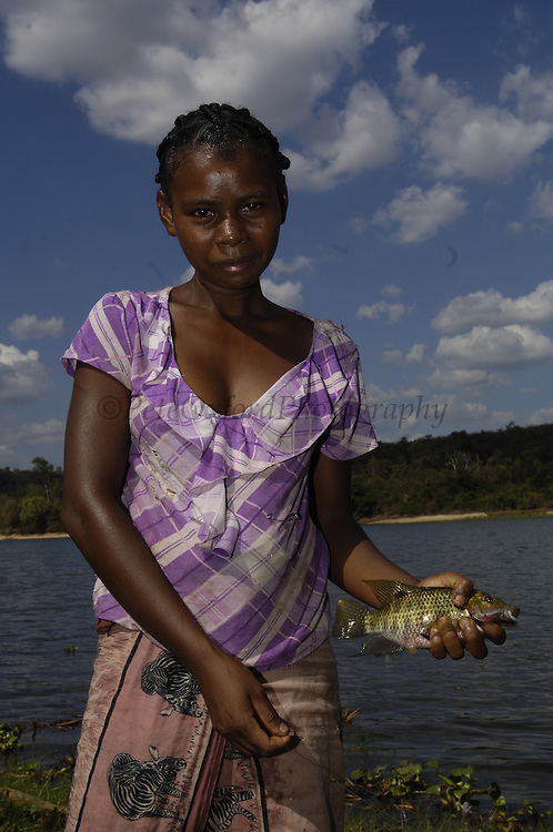 Woman fishing in Lake Ravelobe across from the Ampijeroa Forest Station. Ankarafantsika Nature Reserve, Western deciduous forest. MADAGASCAR<br />Crocodiles have recently started eating people from the village in the area and it is thought that the lake is so over-fished that the crocodiles no longer have enough of their natural food. On New Year's Day the people sacrifice a Zebu and feed it to the crocodiles.