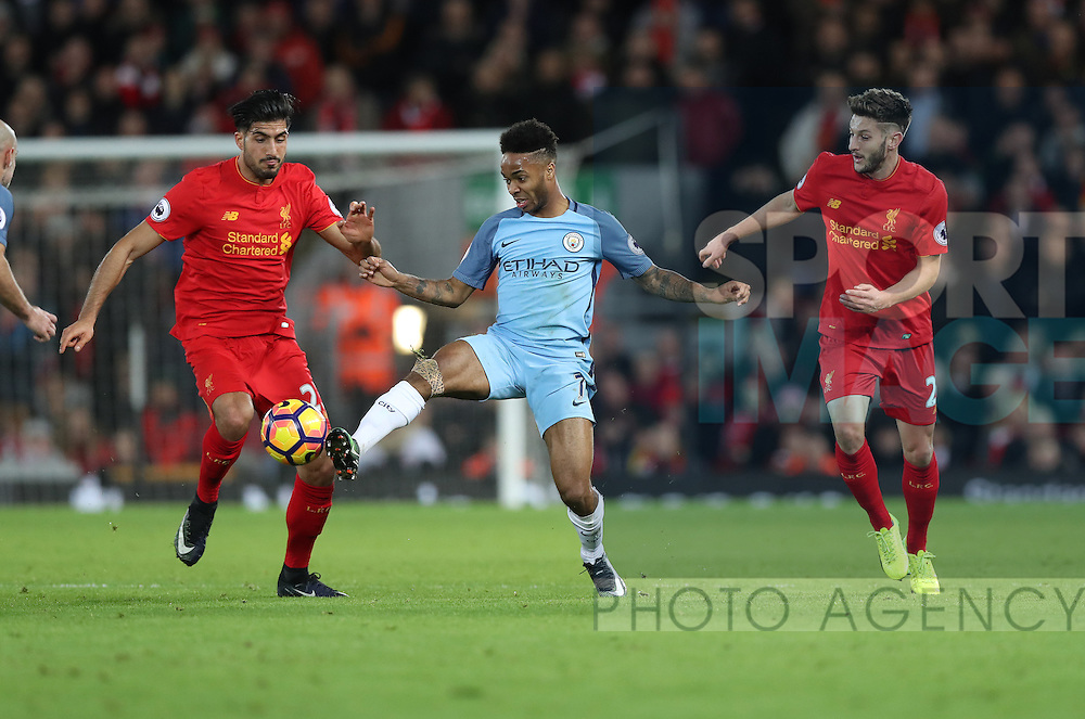 Raheem Sterling of Manchester City is tackled by Emre Can and Adam Lallana of Liverpool during the English Premier League match at Anfield Stadium, Liverpool. Picture date: December 31st, 2016. Photo credit should read: Lynne Cameron/Sportimage