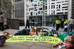 Extinction Rebellion activists stage a die-in outside the Department for Environment, Food and Rural Affairs (Defra) in protest against the pollution of the UK's waterways on 5th August 2021 in London, United Kingdom. The activists were highlighting pollution of rivers by water companies and farms and the failure of the Environment Agency and Defra to protect waterways and to prosecute offenders.
