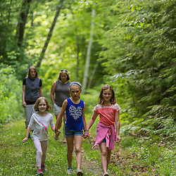 Three girls walk with two women on a trail near Page Pond in Meredith, New Hampshire.