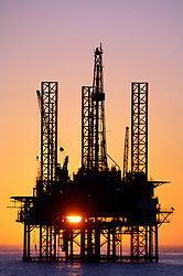 Stock photo of a Jack up oil and gas drilling rig in the Gulf of Mexico at sunset.
