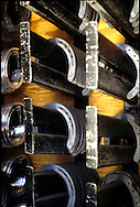 New horseshoes lined up on metal racks on a wooden wall.