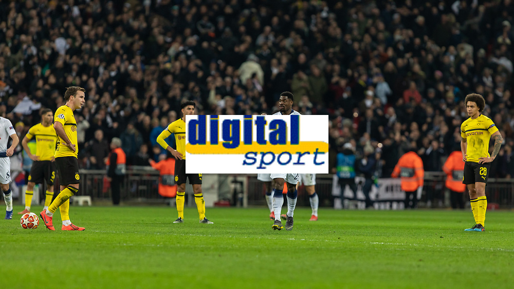 Football - 2018 / 2019 UEFA Champions League - Round of Sixteen, First Leg: Tottenham Hotspur vs. Borussia Dortmund<br /> <br /> Serge Aurier (Tottenham FC)  makes his way back to his half as dejected Dortmund players wait to restart the game at Wembley Stadium.<br /> <br /> COLORSPORT/DANIEL BEARHAM