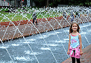 Child (6 years old) standing beside fountain and pool. Darling Harbour, Sydney, Australia