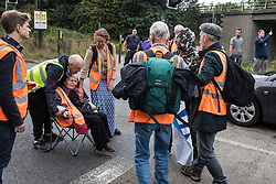 Godstone, UK. 13th September, 2021. A man tries to remove one of several Insulate Britain climate activists blocking a slip road from the M25, causing a long tailback on the motorway, as part of a new campaign intended to push the UK government to make significant legislative change to start lowering emissions. The activists, who wrote to Prime Minister Boris Johnson on 13th August, are demanding that the government immediately promises both to fully fund and ensure the insulation of all social housing in Britain by 2025 and to produce within four months a legally binding national plan to fully fund and ensure the full low-energy and low-carbon whole-house retrofit, with no externalised costs, of all homes in Britain by 2030 as part of a just transition to full decarbonisation of all parts of society and the economy.