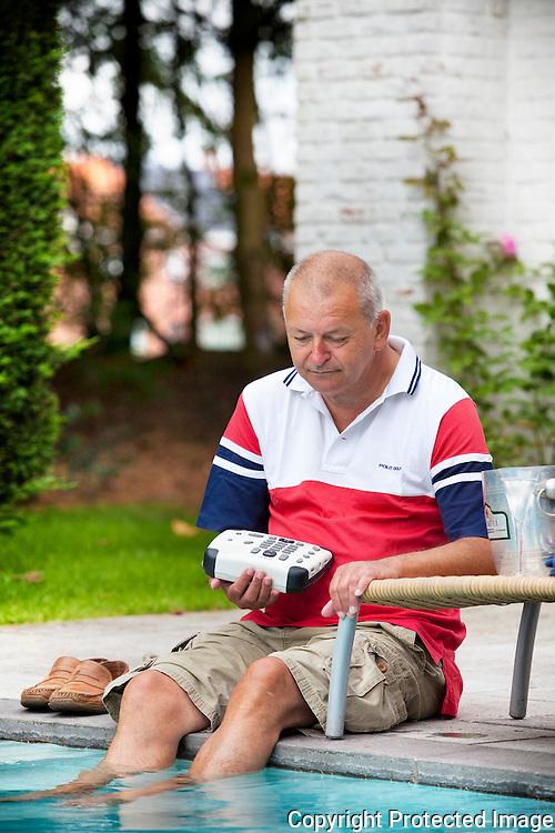 362204-Herman Van Doninck is 90% van zijn zicht kwijt door ziekte, Herman aan het zwembad met zijn Daisyspeler-Leiseinde 14 Turnhout