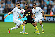 Raheem Sterling of Manchester city © gets in between Gylfi Sigurdsson (l) and Jack Cork of Swansea city.  Premier league match, Swansea city v Manchester city at the Liberty Stadium in Swansea, South Wales on Saturday 24th September 2016.<br /> pic by Andrew Orchard, Andrew Orchard sports photography.