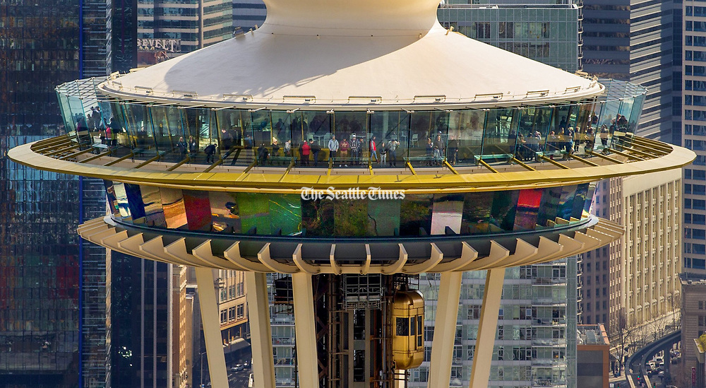 This bird's-eye view of visitors on the Space Needle's observation deck was taken from a helicopter passing by the Seattle landmark. (Mike Siegel / The Seattle Times)