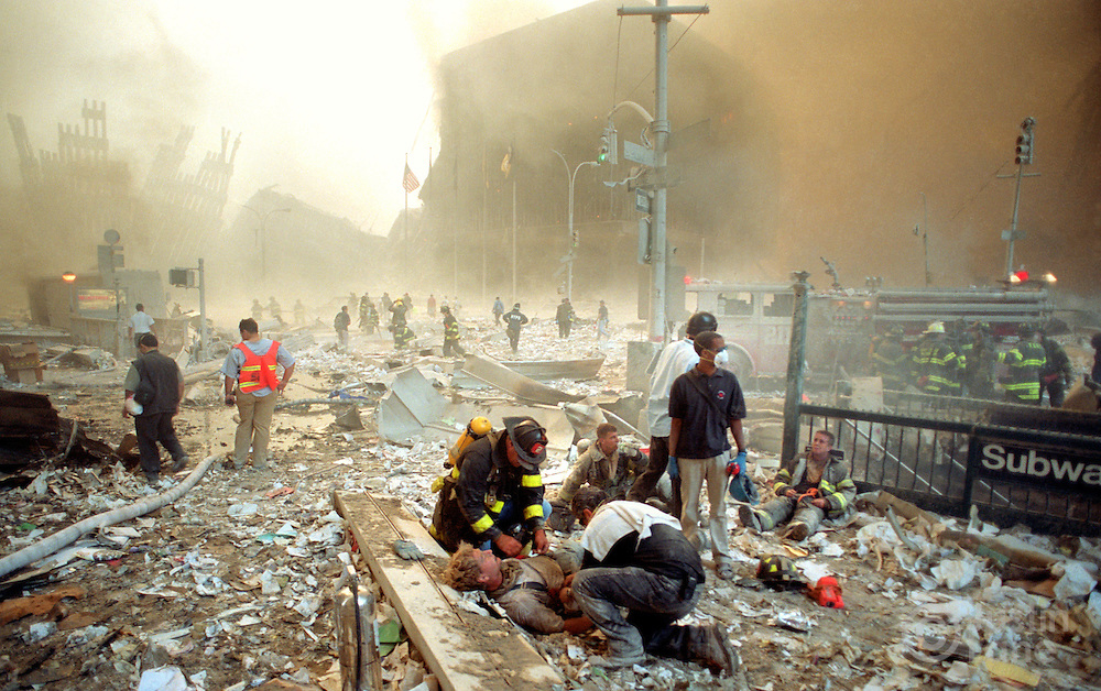 Injured firefighters are treated after collapse of the World Trade Center.<br />This photograph was awarded the 2002 Pulitzer Prize for Breaking News Photography.