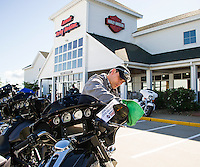 Bradford Thomas joining the Laconia Harley Davidson team from Charlotte, NC this week polishes up this 2016 Street Glide Special on Tuesday morning.  (Karen Bobotas/for the Laconia Daily Sun)