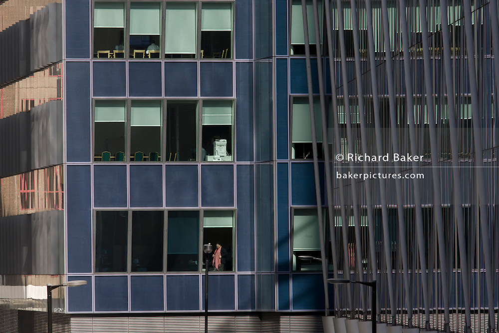 A solitary woman office worker gazes out from her modern office complex in the City of London, the capital's financial district - also known as the Square Mile.