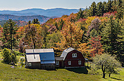 A Vermont farm perched on a hillside overlooking the Green Mountains in their Fall glory.