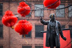 © Licensed to London News Pictures . 22/02/2015 .  Manchester , UK . The statue of William Ewart Gladstone pointing to red lanterns in Albert Square . People cover their heads in the rain . Crowds stand out in the snow to watch Chinese New Year celebrations in Manchester today ( Sunday 22nd February 2015) . Photo credit : Joel Goodman/LNP