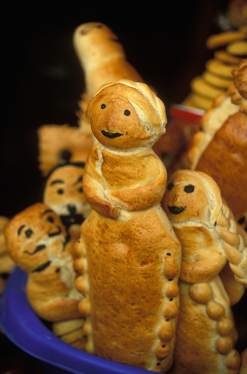 Bread figurines representing dead family members for sale at Todos Santos in Oruro, Bolivia. In the Altiplano of Bolivia, it is customary that a family, in which there has been a death within the last three years, build a shrine at home at Todos Santos, decorating it with religious symbols as well as a picture of the deceased and food and drink that he or she liked, and then call down the spirit for a three day visit. The bread is particularly important. There are pieces of bread shaped like human beings, representing the dead, and there are also pieces with the shape of various old Inca symbols such as the sun and the moon.