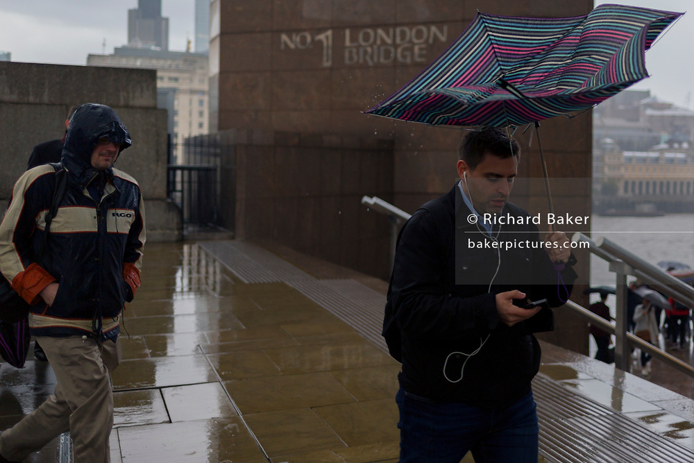 During a spring shower, a male commuter carrying a collapsed umbrella rushes over London Bridge during the evening rush-hour, from the City southwards to Southwark, on 3rd May, in London, England
